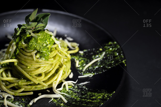 High angle of tasty pasta with pesto sauce and Parmesan cheese served on table in black background