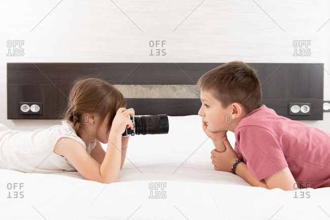 Side view of cute sister taking picture of brother on photo camera while lying on bed at home