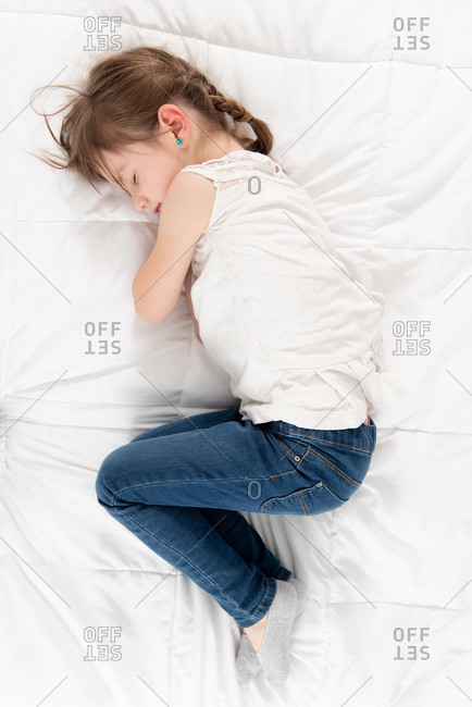 From above side view of adorable child in casual clothes lying on soft bed in flat and resting with closed eyes during weekend at home