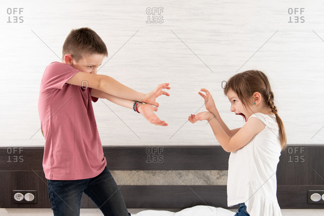 Side view of playful brother and sister having fun on bedroom while entertaining at home during weekend