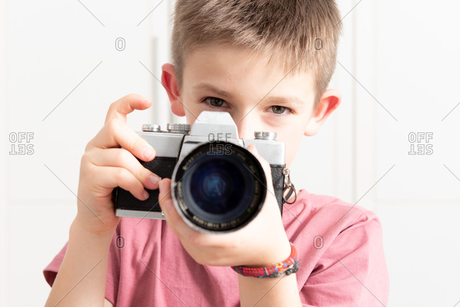 Cute child in casual wear taking photo on retro camera while standing in modern apartment and entertaining during weekend