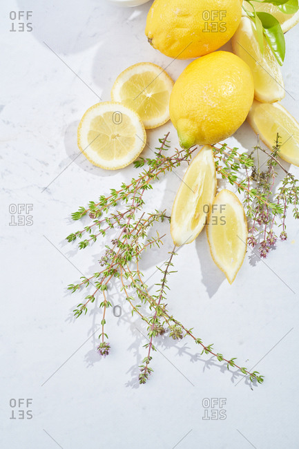 Top view of fresh green thyme and cut lemons prepared for making fresh natural drink placed on white marble table