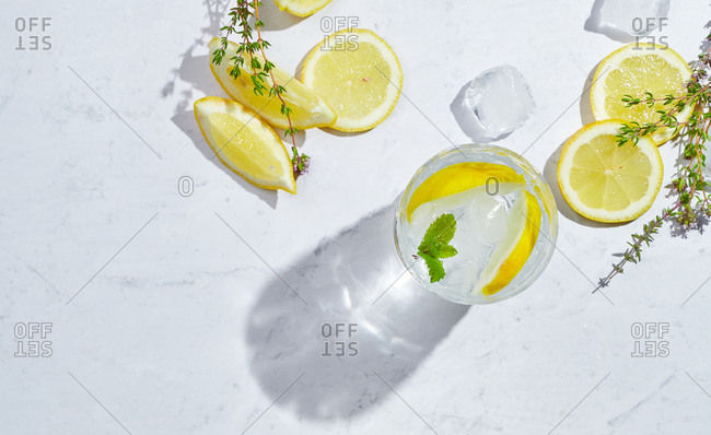 From above glasses with refreshing cold thyme and ginger lemonade with slices of lemon and mint leaves served on table in light room