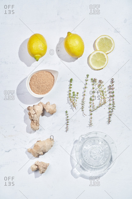 Top view set of various ingredients for recipe of healthy refreshing ginger and thyme lemonade arranged on white marble table
