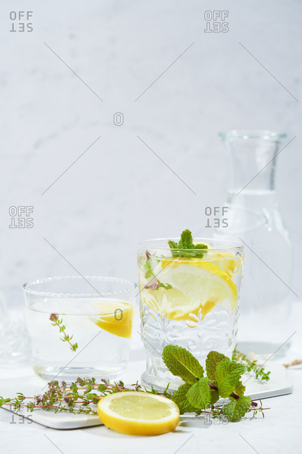 Glasses with refreshing cold thyme and ginger lemonade with slices of lemon and mint leaves served on table in light room