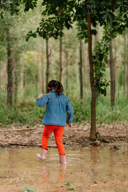 Back view of unrecognizable cute child in rubber boots standing in dirty water in puddle while having fun during weekend