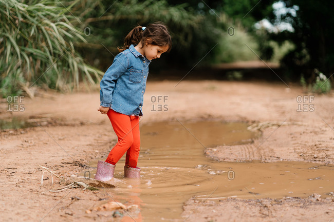 Side view of cute child in rubber boots standing in dirty water in puddle while having fun during weekend