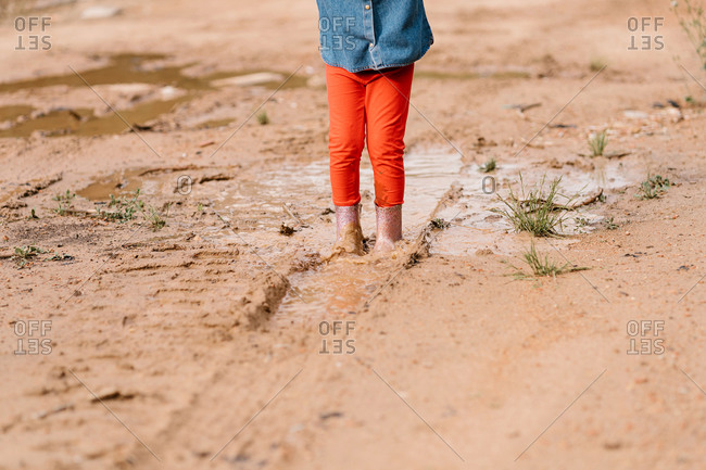 Cropped unrecognizable cute child in rubber boots standing in dirty water in puddle while having fun during weekend