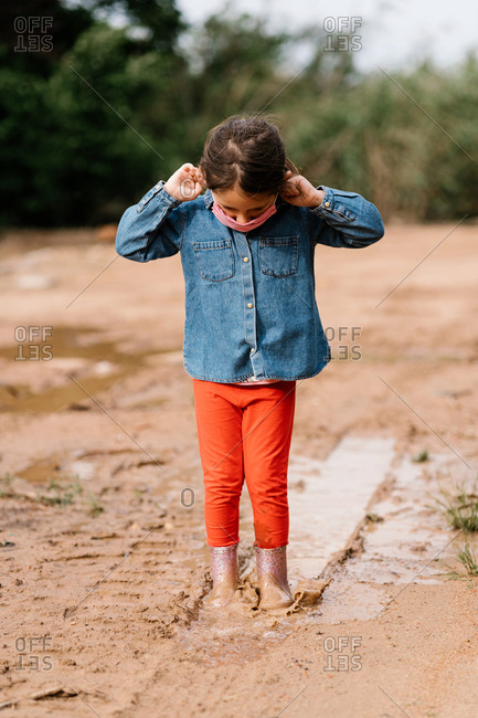 Cute child in rubber boots and surgical mask standing in dirty water in puddle while having fun during weekend