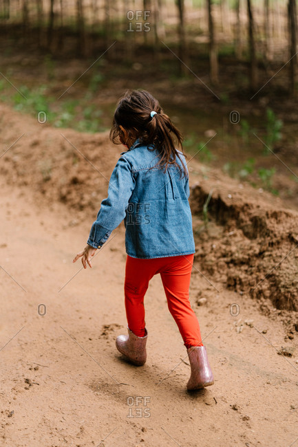 Back view of unrecognizable cute child in rubber boots strolling in mud path near dirty puddle