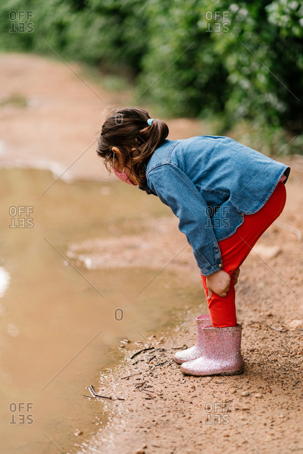 Side view of cute child in rubber boots and surgical mask standing in dirty water in puddle while having fun during weekend