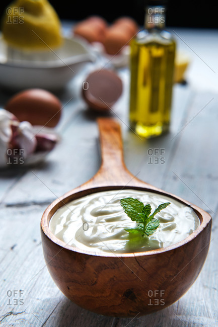 Giant wooden spoon with sour cream and bottle of olive oil placed on table with garlic and fresh lemon