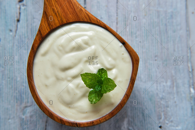 Giant wooden spoon with sour cream with fresh mint placed on table
