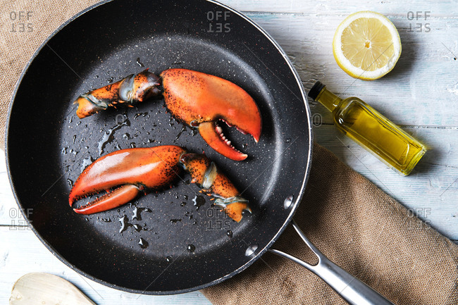 From above of yummy lobster claws in pan placed on table with bottle of olive oil and half of juicy lemon
