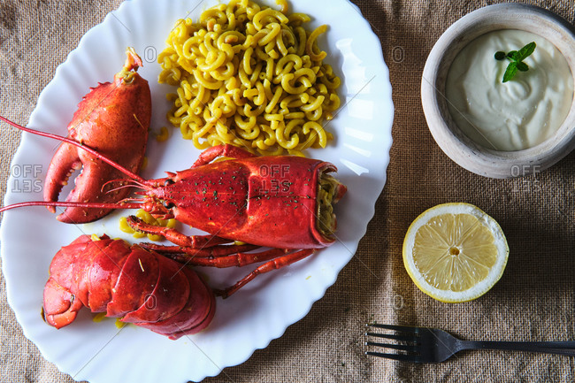 Top view of tasty lobster served with pasta and placed on table with bowl of sour cream and half of lemon