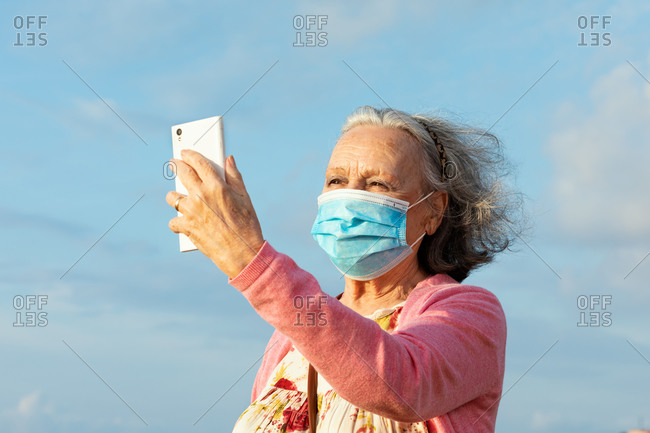 Senior female in sterile mask and casual wear taking selfie on cellphone while standing under blue cloudy sky outdoors during quarantine time