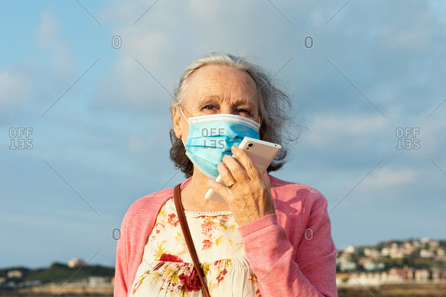 Senior female in sterile mask and casual wear talking phone while standing under blue cloudy sky outdoors during quarantine time