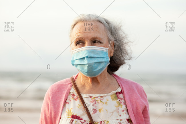 Senior gray haired lady in blue sterile mask and casual clothes looking away while standing on blurred background in daylight