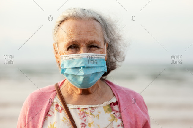 Senior gray haired lady in blue sterile mask and casual clothes looking at camera while standing on blurred background in daylight