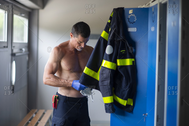 Serious fireman with naked torso and in latex gloves standing with respirator face mask near locker at fire station while preparing for work