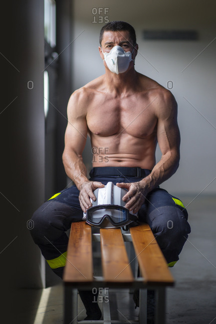 Strong mature male firefighter with naked torso sitting on bench in mask and holding a helmet while looking at camera