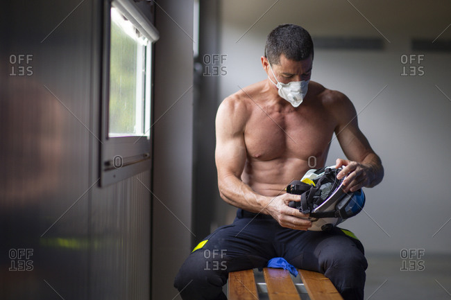 Strong mature male firefighter with naked torso sitting on bench in mask and holding a helmet while looking away