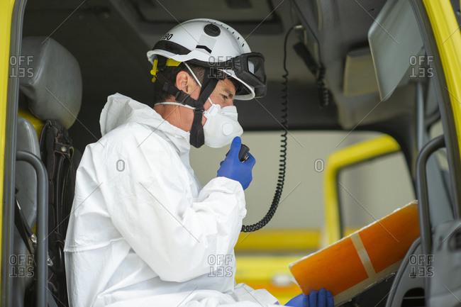 Side view of fireman wearing protective uniform and hard helmet with medical gloves sitting in fire engine speaking on walkie talkie