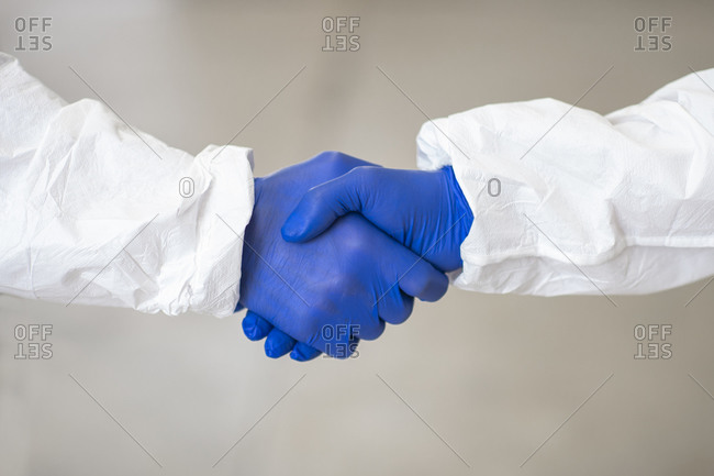 Side view of unrecognizable coworking practitioners in costumes and medical gloves shaking hands during coronavirus epidemic