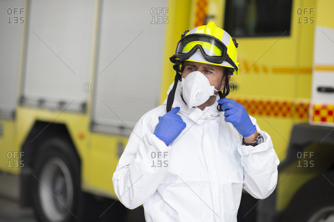 Serious fireman in protective costume and wearing respirator on fire station during coronavirus pandemic