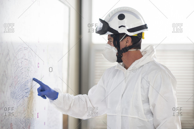 Side view of fireman wearing protective costume and respirator standing at fire station and pointing at paper map attached to wall