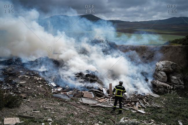 Back view of brave fireman in protective uniform standing with hose and extinguishing fire on dump in mountains