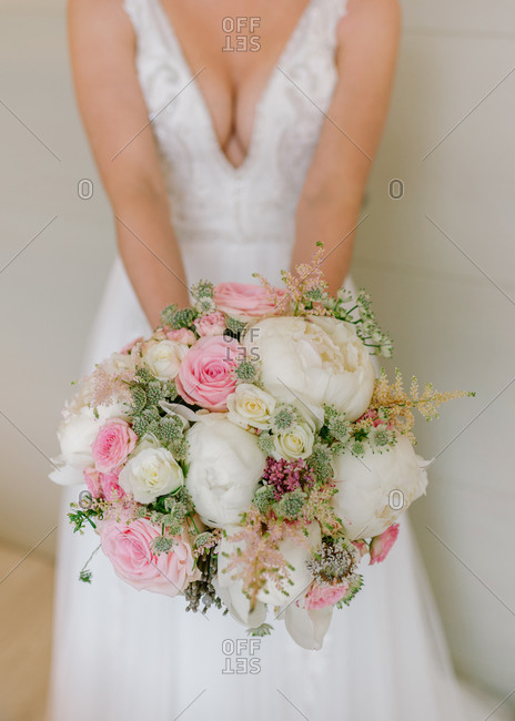 Unrecognizable female in wedding dress standing in room with bunch of fresh flowers