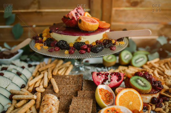 Delicious cheesecake on tray garnished with various fruits served on table with assorted food