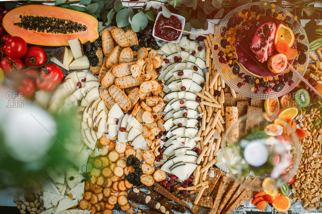 Top view of assorted cheese and crackers placed on table with pastry and fresh fruits