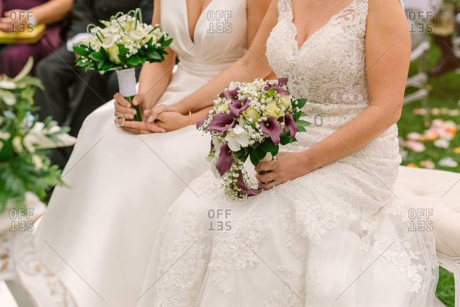 Crop newlywed gay couple in elegant wedding dresses sitting with tender bouquets during wedding day