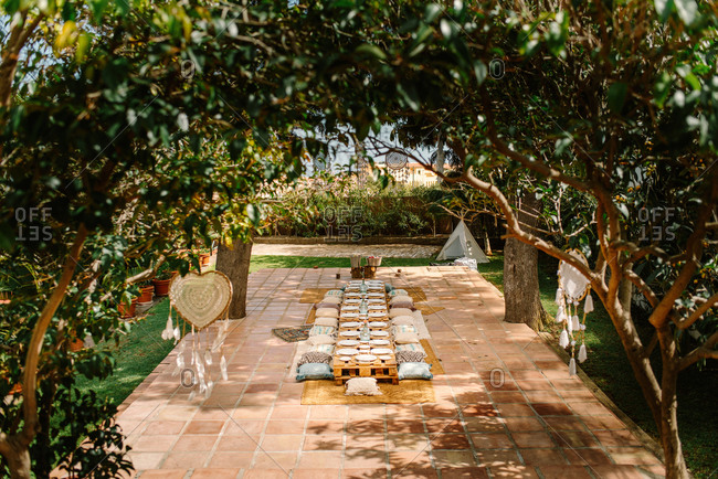 Summer terrace with wooden pallets in shape of tables and cozy pillows prepared for celebration