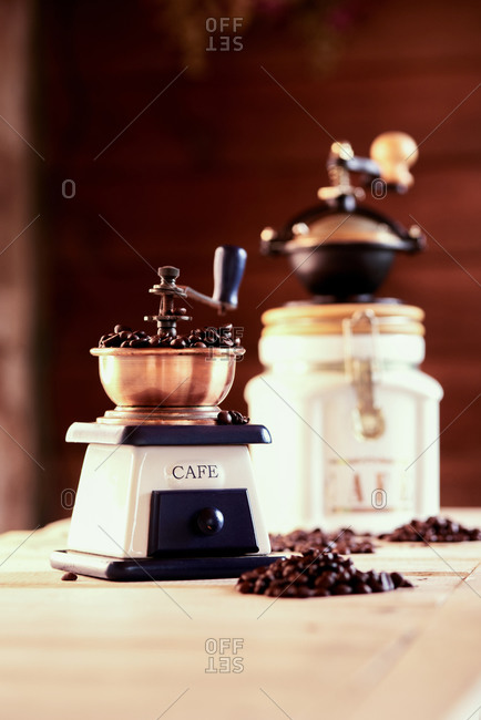 Vintage manual mills with coffee beans placed on wooden table in cozy cafeteria