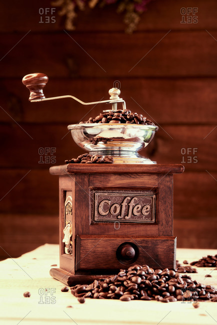 Vintage manual mill with coffee beans placed on wooden table in cozy cafeteria