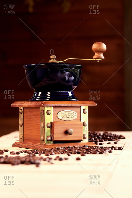 Manual coffee mill placed on table with scattered coffee beans in cozy cafe