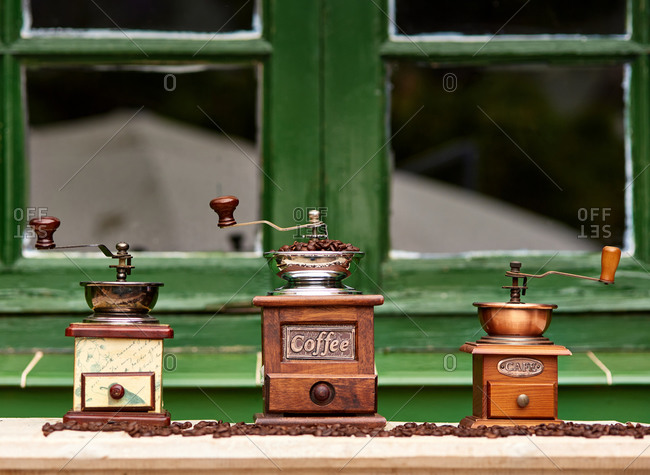 Vintage manual mills with coffee beans placed on wooden table in front of a window of cozy cafeteria