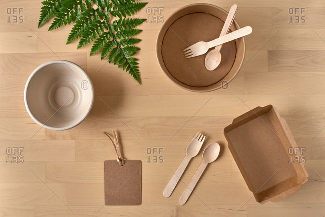 Top view of recyclable carton food package and wooden fork and knife placed on table with fern leaf