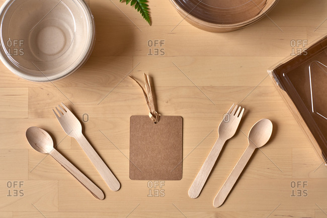 Top view of recyclable carton food package and wooden fork and knife placed on table with fern leaf and blank label