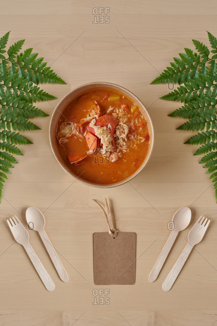 Top view of tasty rice and lobster with gravy served in cardboard bowl and placed on wooden table with disposable utensils