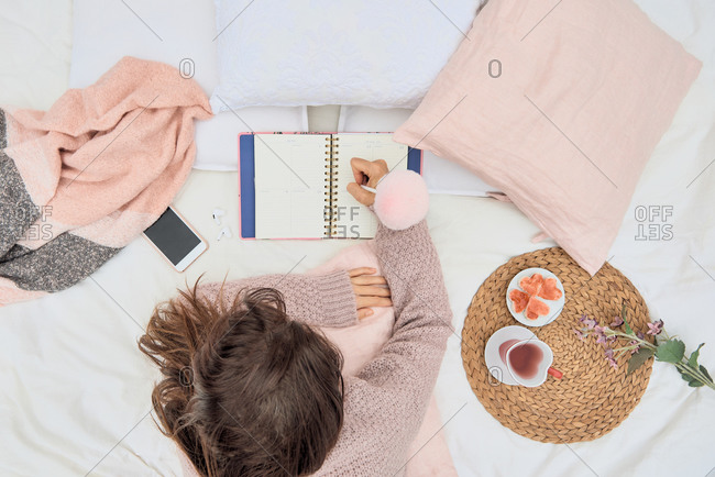 Top view of female wearing soft sweater lying on bed with cushions and tea while writing thoughts in notebook