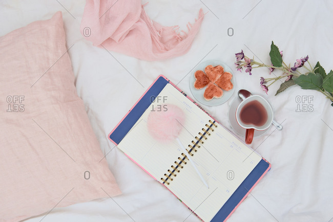 Top view of opened daily planner composed with cup of hot tea and tasty cookies placed on soft bed with flowers and cushion
