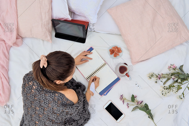 Top view of self employed female in knitted wear lying on soft bed and browsing tablet while writing notes in planner during remote work from home