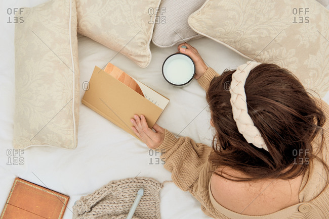 From above of unrecognizable female in knitwear lying on comfortable bed with cup of milk and enjoying interesting story