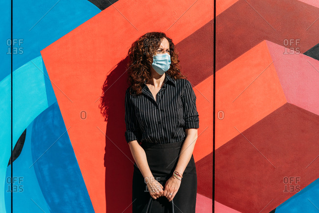 Woman wearing a mask due to an outbreak and leaning on a blue and red painted wall.