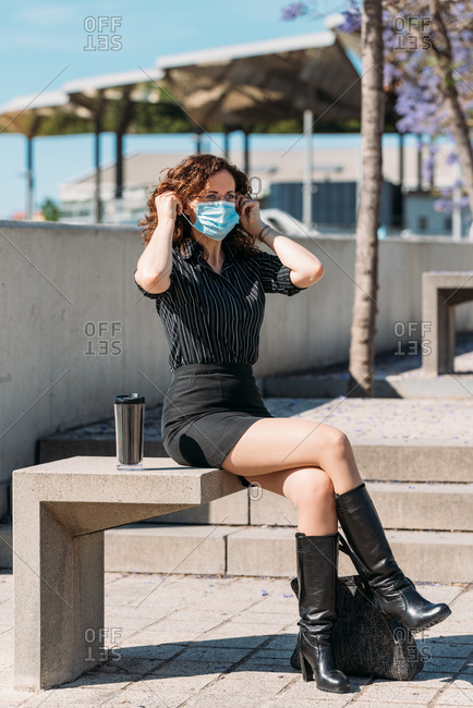 Office worker on a coffee break seating on a park bench and adjusting her mask.