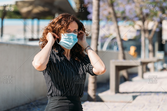 Woman on the street adjusting her mask during a virus outbreak.